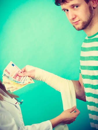 bribery: Corruption in healthcare industry. Female doctor bandaging male hand. Man giving money to woman. Bribery in medicine. Stock Photo