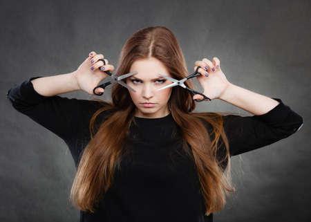 Le style et la mode. Professional barbier coiffeur avec une nouvelle idée de changement de look. Longue femme aux cheveux avec des ciseaux créant coiffure coiffure.