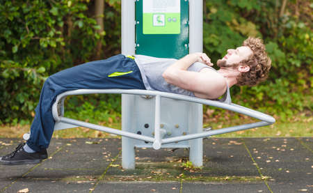 Active young man exercising on bench. Muscular sporty guy in training suit working out at outdoor gym. Sport fitness and healthy lifestyle concept.