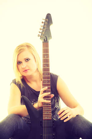 beginner: Music concert and show. Blonde pretty woman artist playing rock roll on electrical guitar. Young girl feels like star. Star beginner creating sounds song.