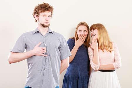 mislead: Young women friends talking gossiping about man. Two women whispering sharing secret news. Stock Photo
