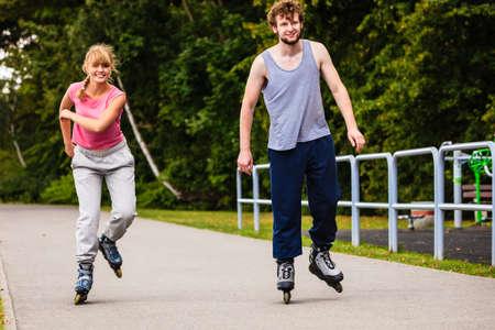 Hobby y pasar el tiempo libre en verano. El deporte y el ejercicio. cuerpo sano y el bienestar. Pareja tiene diversión juntos patinar al aire libre.
