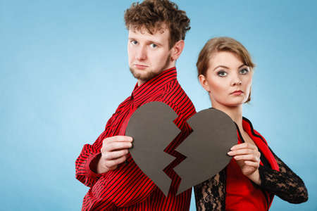breaking up: Break up and leave in relationship. Negative emotions between people in love. Young couple with two halves of broken heart. Lovers breaking up.