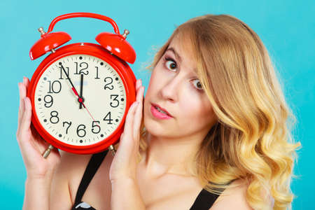 punctuality: Management time concept. Blonde girl serious pensive face expression with alarm clock on blue. Foto de archivo