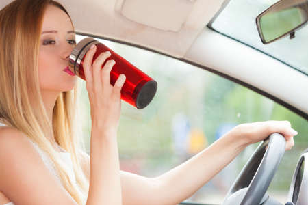 Take an energy boost. Young attractive woman sitting at the wheel drinking hot tea or coffee from vacuum flask bottle while driving the car.