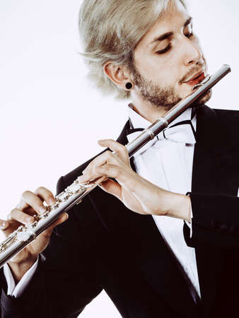 woodwind: Classical music study concept. Male flutist musician performer playing flute. Young elegant man wearing tailcoat holds instrument Stock Photo