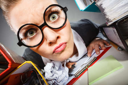 insane insanity: Workaholism mental insanity weird job work company concept. Insane office woman at work. Mad secretary making silly expression lurking through her desk.