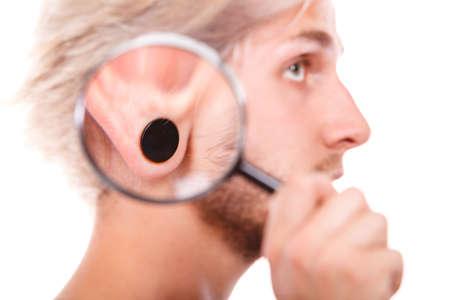 Stylish teenage boy close face profile, pierced ear black plug through the magnifying glass, isolated on white Stock Photo
