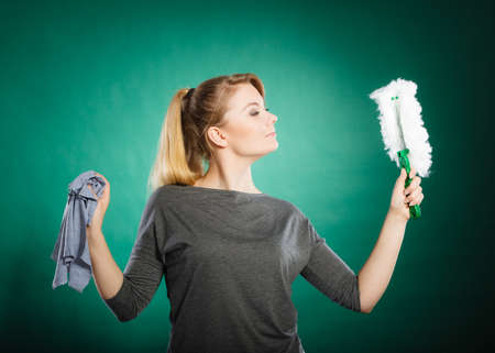 domestic chores: Household duties concept. Young energy girl playing with cleaning cloth doing domestic chores. Cheerful playful housewife ready to clean house. Stock Photo