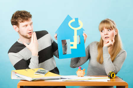Money and real estate problems. Young worried couple with paper model of house and key. Young marriage calculate expenses. Stock Photo