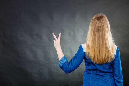 expresion corporal: Positividad y el concepto de éxito. Vista posterior de la mujer rubia con el pelo largo y recto. Muchacha que muestra el pulgar hacia arriba gesto. La expresión corporal.