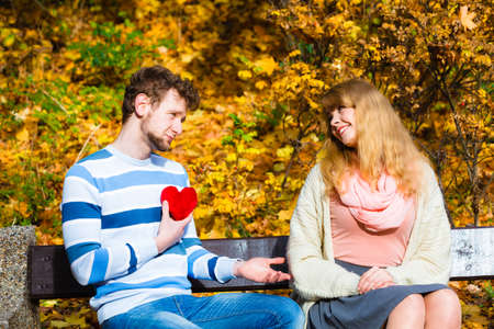 confessing: Accepting and sharing feelings. Confessing love and affection with romantic gesture. Positive reaction. Pair sit on bench in park man present plush heart toy to happy girl.