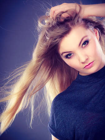 haircare: Hairstyle and haircare concept. Portrait of blonde charming attractive young lady with open waving hair. Woman with healthy and beauty hairdo coiffure. Stock Photo