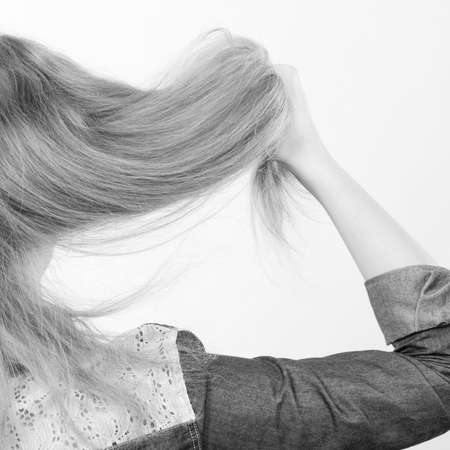 back straight: Hairstyle and hairdo. Haircare concept. Back view of blonde woman playing with straight long hair. Hairstylist barber making coiffure.