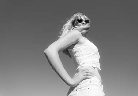 blackwhite: Summer, happiness and lifestyle concept. Lovely blonde girl in sunglasses relaxing outdoor against blue sky, wide angle unusual view