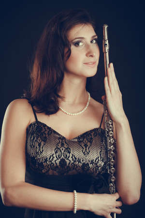 transverse: Music performance. Stunning elegant young lady with transverse flute instrument on black. Woman preparing to her solo show in theater opera.
