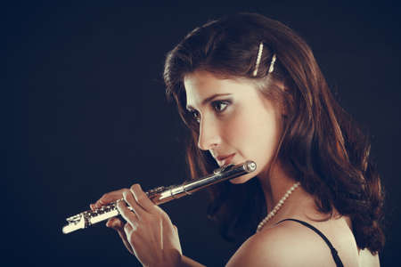 alluring: Music and elegance. Alluring elegant woman playing on transverse flute. Female musician with her instrument performing.