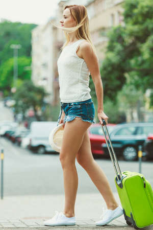 beginnings: Leaving and new beginnings. Young blonde woman with luggage green suitcase move out from family house. Female student looking for flat apartment in big city. Stock Photo