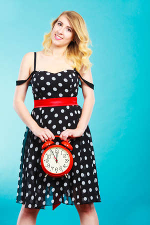 Management time concept. Blonde fashion girl wearing black dotted dress smiling face expression with alarm clock on blue. Stock Photo