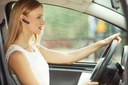 handsfree phones: Transport and safety concept. Young blonde woman driving car using her mobile phone and headset, side view Stock Photo