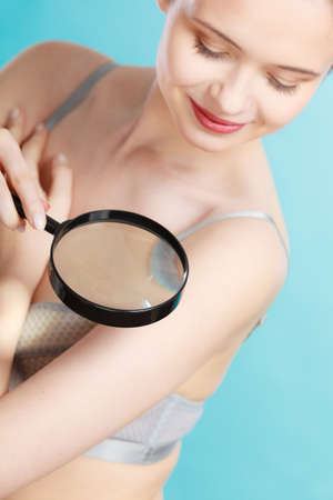 moles: Skin control self examination concept. Yound woman holds magnifying glass in hand examining her body for melanoma suspicion. Checking benign moles.