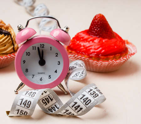 Gluttony and not eat junk sugar foods concept. Time for slimming. Cake cupcakes measuring tape and alarm clock on kitchen table Stock Photo