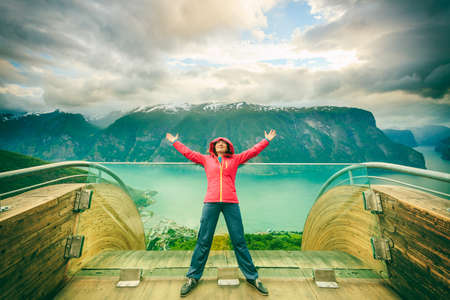 raised viewpoint: Tourist woman on Stegastein viewpoint enjoying Aurland fjord view with arms raised outstretched up, Sogn Og Fjordane, Norway