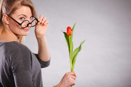 red tulip: Happiness and satisfaction with life. Blonde woman wearing eyewear with single red green tulip. Happy joy girl feeling spring time holding beautiful flower. Stock Photo