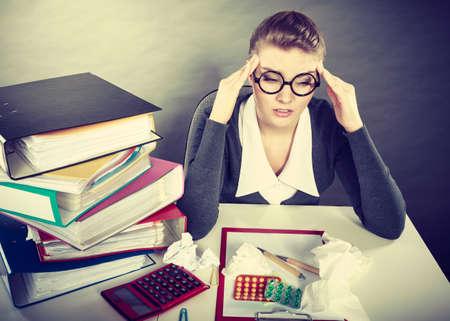 La fatigue et le concept de la douleur. Jeune femme d'affaires élégante avec beaucoup de pilules pour les maladies et les douleurs. Fatigué comptable femme blonde malade au travail.