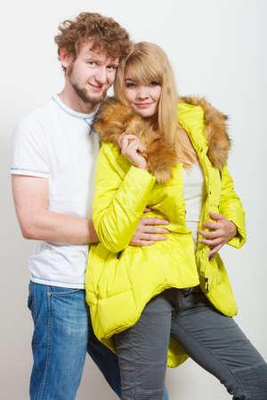 warm shirt: Happy joyful couple posing in studio. Young woman in warm lime jacket and man in white shirt. Winter autumn fall fashion.