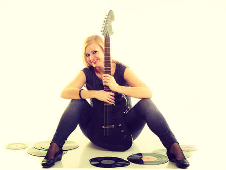 electronical: Music retro style. Young rock roll female star holds playing electric guitar surrounded by vinyl record. Classical audio collection.