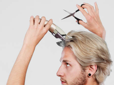 metrosexual: Hairdo changing hairstyle concept. Cool male hairstylist making self trendy haircut, fashion blonde metrosexual model going to shave his long hair, using shaver and scissors