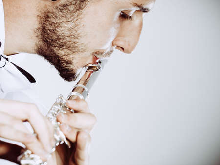 professional flute: Flute music playing professional male flutist musician performer. Young elegant stylish man with instrument, close up