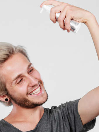 metrosexual: Hairdo haircare and makes hairstyle concept. Handsome young guy, fashion blonde metrosexual model applying spray cosmetic to his hair Stock Photo