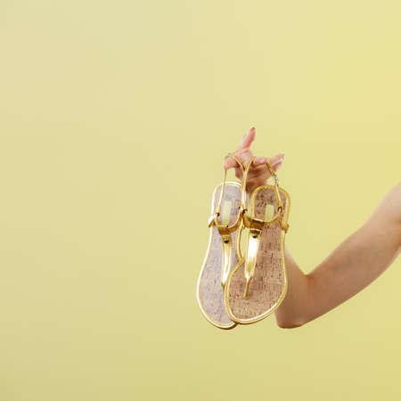 woman sandals: Holidays summer fashion concept. Woman holding golden sandals in hand bright background copy space Stock Photo