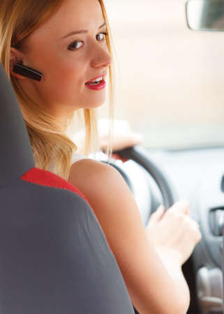 handsfree telephone: Transport and safety concept. Young blonde woman driving car using her mobile phone and headset, side view Stock Photo