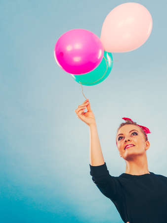 handkerchief: Joy fun and freedom concept. Blonde smiling woman with colorful latex balloons flying balls. Retro fashion styled girl portrait. Stock Photo