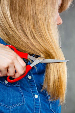 Cutting coiffure and new look. Part body blonde woman cut her long straight hair. Female hands with red scissors making modern hairstyle. Stock Photo