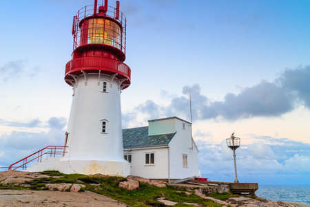 scandinavia: Historic red white lighthouse on the edge of rocky sea coast, South Norway, Lindesnes Fyr beacon Stock Photo