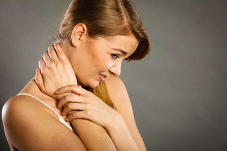 Feeling exhausted, back and spine disease. Woman having bad ache. Female placing hands on her neck suffering from pain