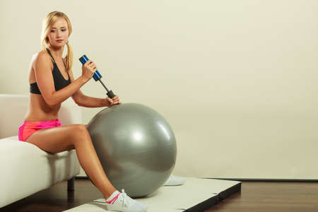 inflating: Sport, training, gym and lifestyle concept. Young attractive slim woman in sportswear with air pump inflating fit ball, fitness exercise
