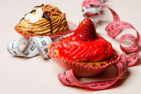 Appetite and gluttony concept. Fattening problem. Cakes cupcakes with measuring tapes on table
