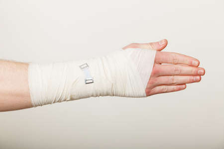 white bandage: Fractures and dislocations concept. Male hand in white bandage. Helpful medication for painful palm arm of young man. Stock Photo