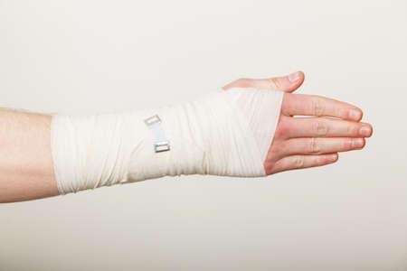 luxacion: Las fracturas y dislocaciones concepto. Mano masculina en el vendaje blanco. medicamentos útiles para el brazo de palma dolorosa de la joven.