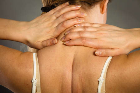 back ache: Feeling exhausted, back and spine disease. Woman having bad ache. Female placing hands on her neck suffering from pain, closeup