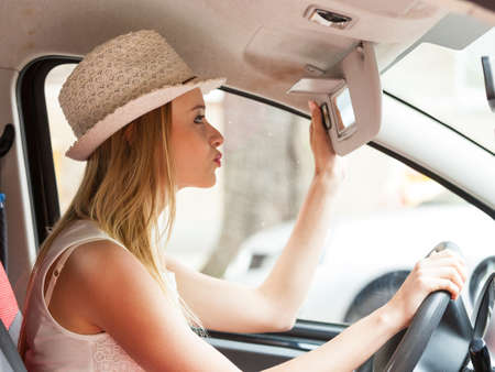 reckless: Distracted driver. Young attractive woman looking in mirror while driving the car.
