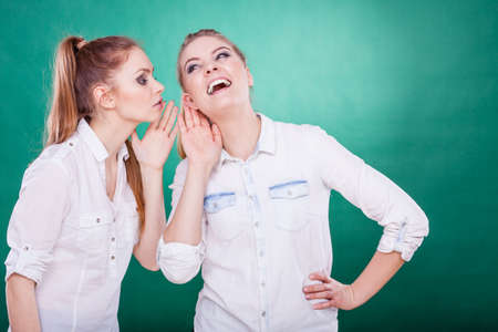 gossiping: Young woman telling her friend some secrets, two women talking gossiping. Excited emotional girl whispering to human ear