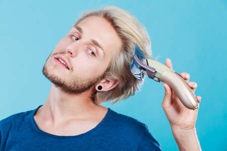 Hairdo hairstyle concept. Cool male hairstylist making self trendy haircut, fashion blonde metrosexual model going to shave his long hair Stock Photo