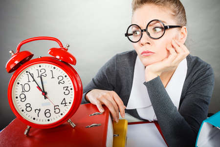 Paper work against time. Young expressive woman in office with big red clock. Unhappy businesswoman so far to ending her work. 版權商用圖片