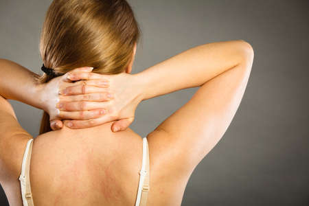 back ache: Feeling exhausted, back and spine disease. Woman having bad ache. Female placing hands on her neck suffering from pain